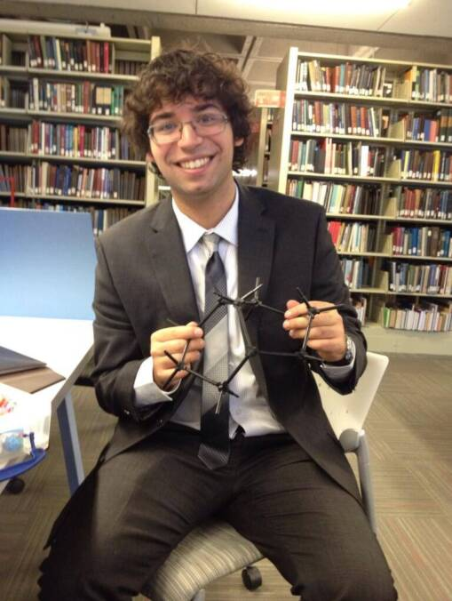 An image depicting Joseph Szymborski in a suit and tie in a library holding a molecular stick model.